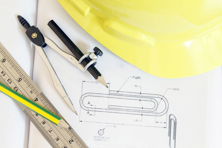 Close-up of blueprints with instruments and hardhat