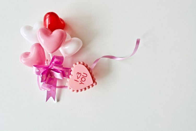 Close-up of heart shape on pink flower over white background