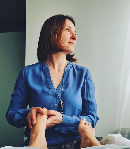 Young woman looking away while doing reflexology