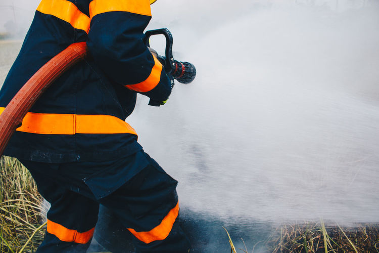 Rear View Of Firefighter Spraying Water On Field