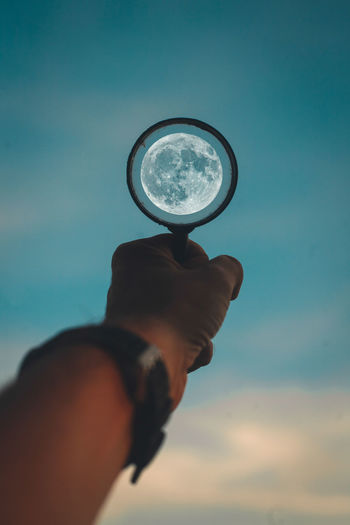 focus on the big thing Hand Human Body Part Holding One Person Sky Real People Unrecognizable Person Magnifying Glass Body Part Lifestyles Cloud - Sky Nature Day Men Human Finger Finger Blue Moon