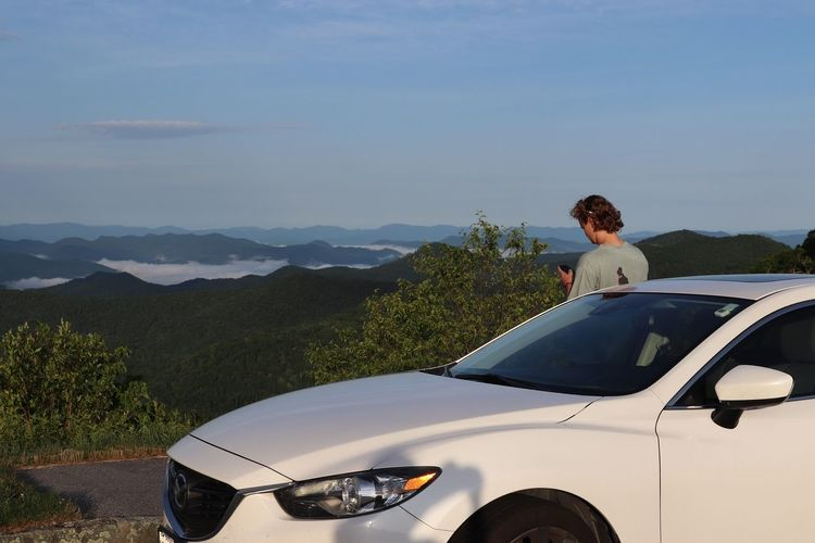 Woman standing by car on mountain against sky