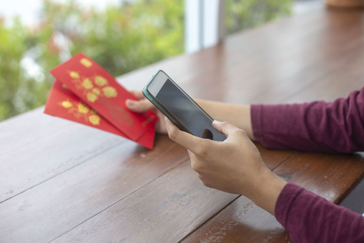 Cropped hands of person using mobile phone while holding greeting cards on table