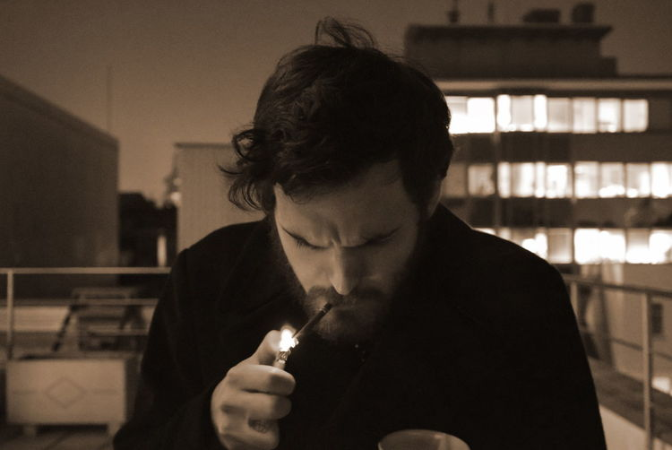 Close-Up Of Man Lighting Cigarette On Terrace