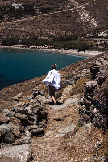 Rear View Of Woman Walking On Mountain Trail Leading Towards Sea