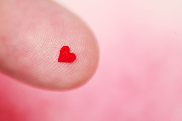 Close up of red love heart on finger tip