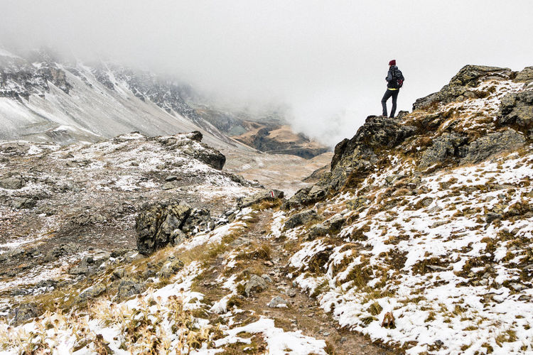 Lost In The Landscape Adventure Backpack Beauty In Nature Climbing Day Exploration Fog Hiker Hiking Leisure Activity Lifestyles Low Angle View Mountain Nature One Person Outdoors Real People Rear View RISK Rock - Object Scenics Standing Winter