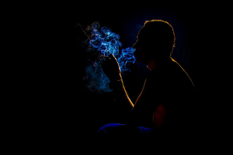 Man Smoking Cigarette Against Black Background