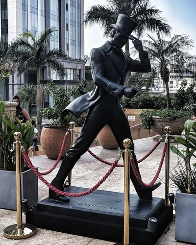 can you name him? Alcohol Drinks Johny Walker City Statue Sculpture Full Length Tree Architecture Sky Building Exterior Built Structure Fictional Character Street Art