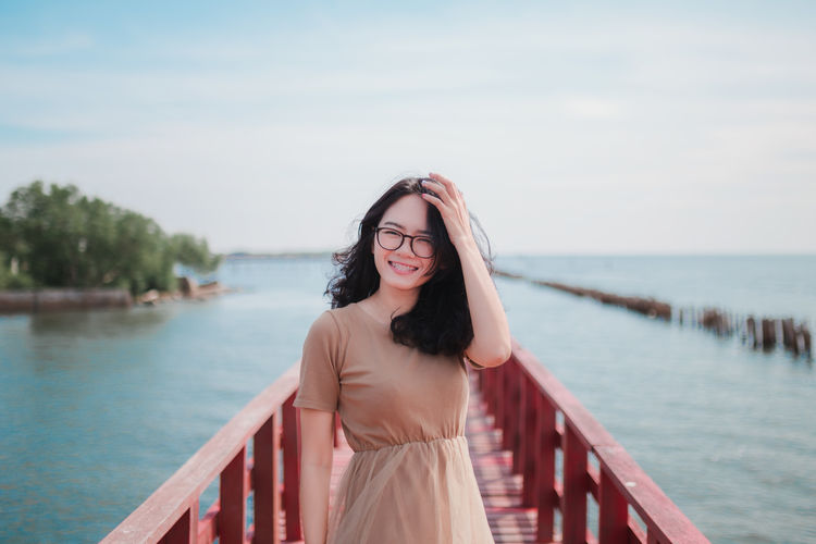 Portrait of smiling beautiful woman standing on footbridge over sea at beach