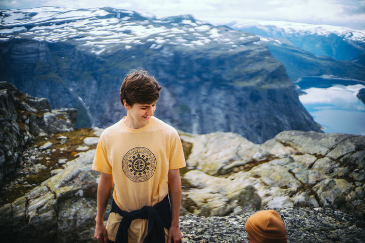 High Angle View Of Young Man Smiling While Standing At Trolltunga During Winter