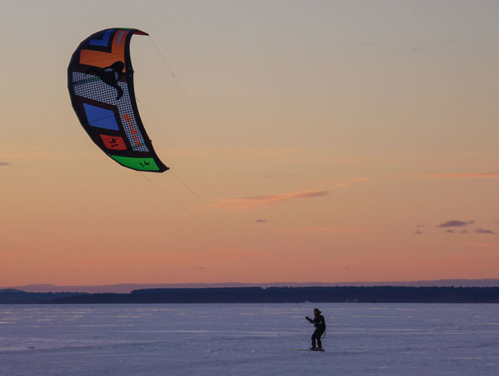 Man kiteboarding on snowcapped field at sunset