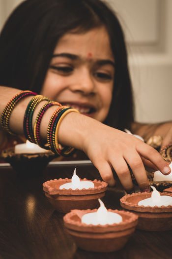 Smiling girl burning diya at home