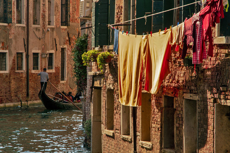 Clothes drying on wooden post in canal amidst buildings