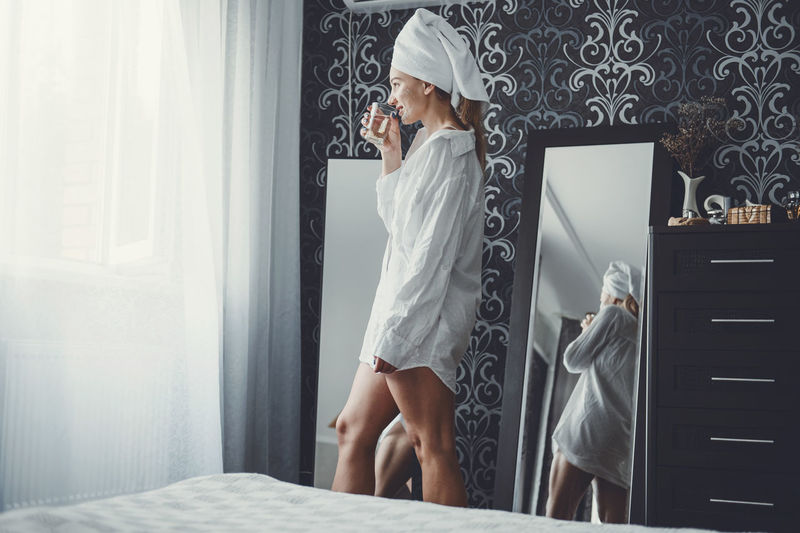 Woman with face mask drinking water while standing by bed at room