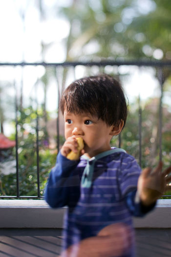 Cute Boy Eating Food While Looking Away On Balcony