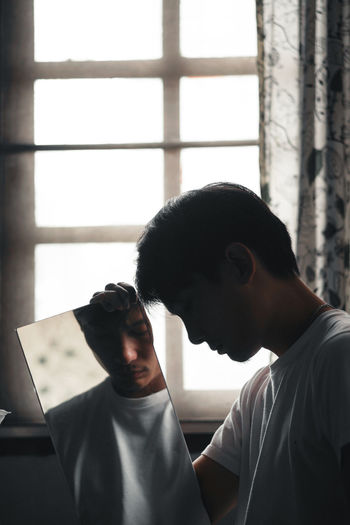 Man holding mirror against window at home