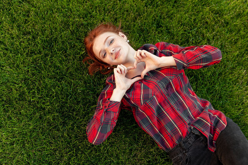 Portrait Of Smiling Teenage Girl Making Heart Shape While Lying On Grassy Field