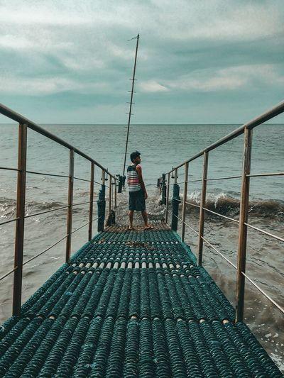 Man standing on railing against sea