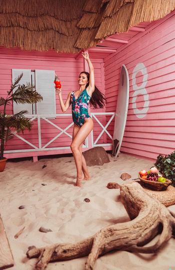 Full length of woman wearing bikini standing on beach