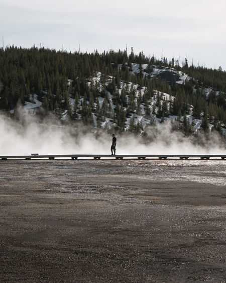 Man standing on boardwalk by geyser at yellowstone