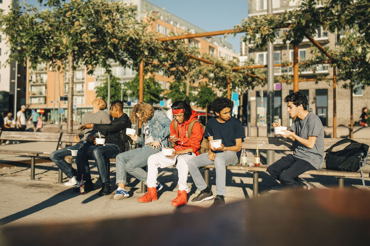 Group of people sitting on seat in city