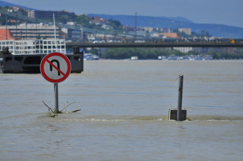 Road Sign Amidst Water During Flood In City