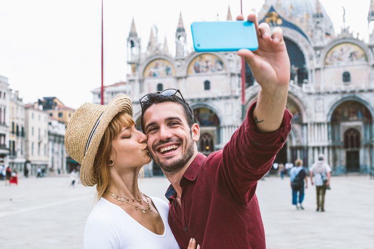 Portrait of smiling man photographing woman in city