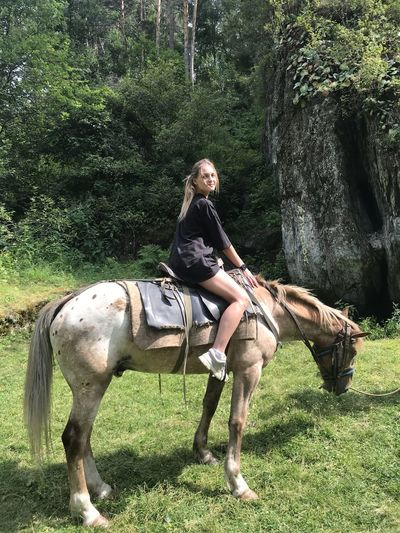 Full length of young woman riding horse on field