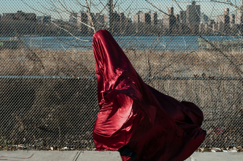 Person Wrapped In Red Fabric While Walking On Footpath By Chainlink Fence In City