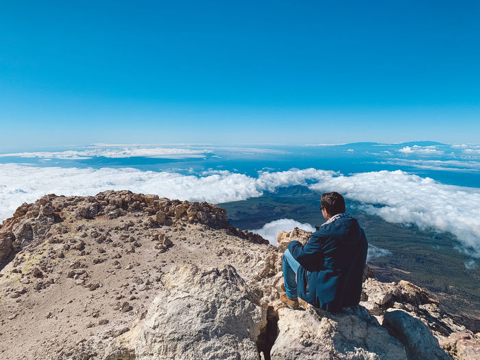 Rear view of man sitting on rocks against blue sky