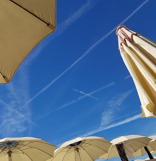 Low angle view of parasols against blue sky