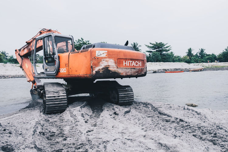 Sept. 26, 2015 - A crawler excavator at rest on the riverbank Construction Excavator Industry Machine Orange At Rest Compact Crawler Digging Equipment Excavation Foot Print Heavy Equipment Minimal Nature Operation Outdoors River Rotating Sand Sky Transportation Truck Vehicle Illustrative Editorial in General Santos, Philippines Breathing Space Investing In Quality Of Life The Week On EyeEm The Photojournalist - 2018 EyeEm Awards #urbanana: The Urban Playground