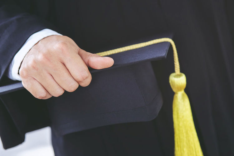 Midsection of student holding mortarboard
