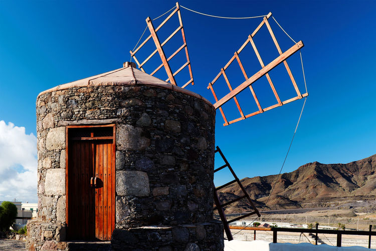 Traditional Windmill At By Mountains Against Blue Sky