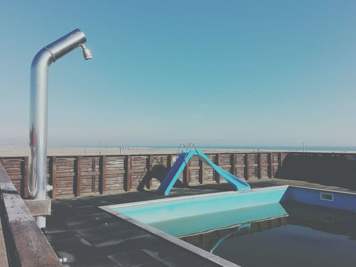 Swimming pool at beach against clear sky