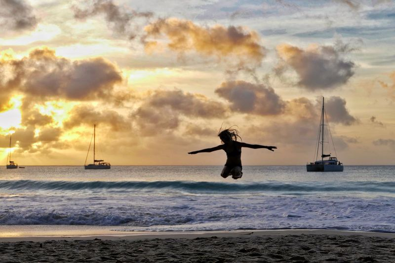Man jumping at beach against sky during sunset