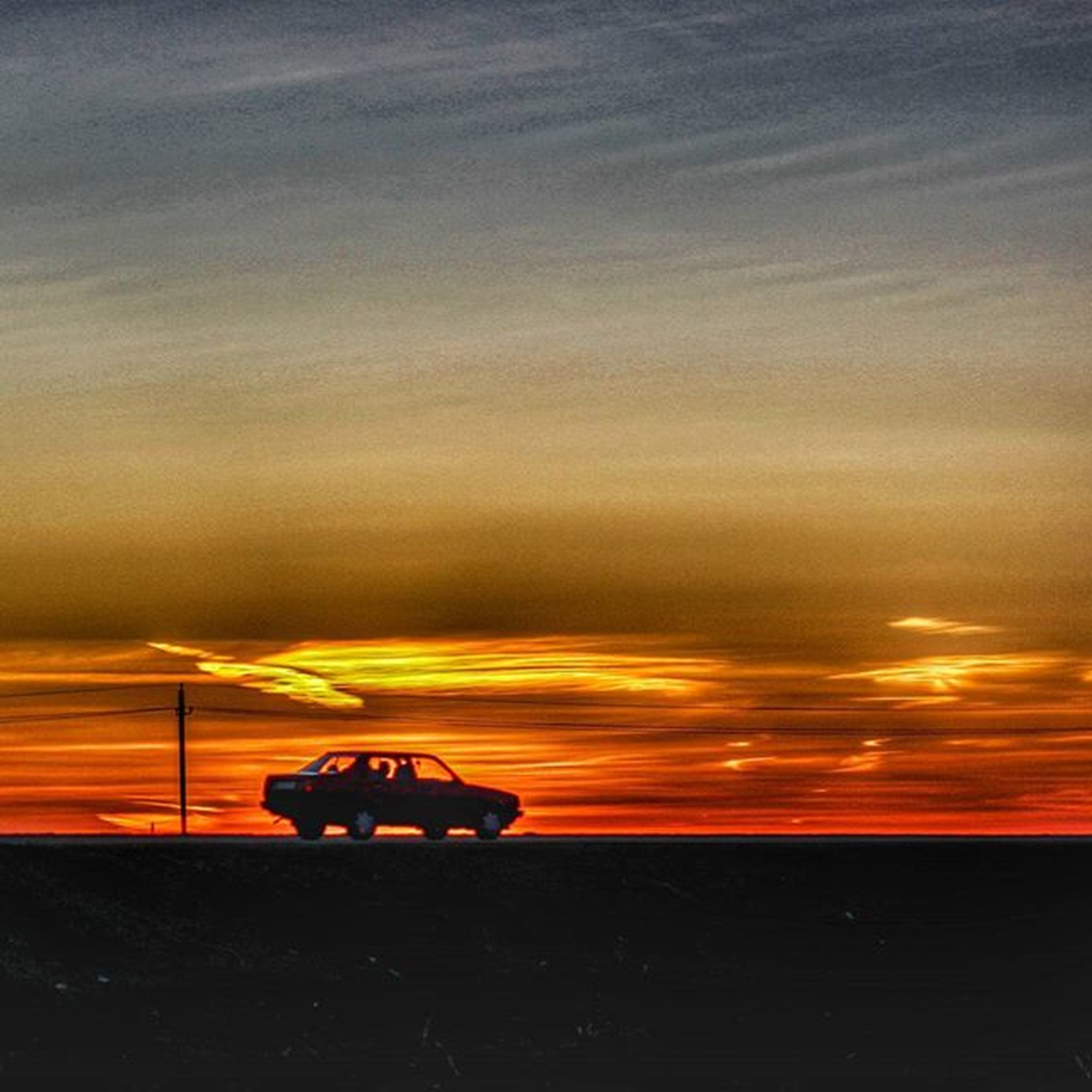 sunset, transportation, orange color, mode of transport, land vehicle, sky, silhouette, scenics, cloud - sky, beauty in nature, sea, tranquility, car, nature, tranquil scene, travel, horizon over water, idyllic, water, dramatic sky