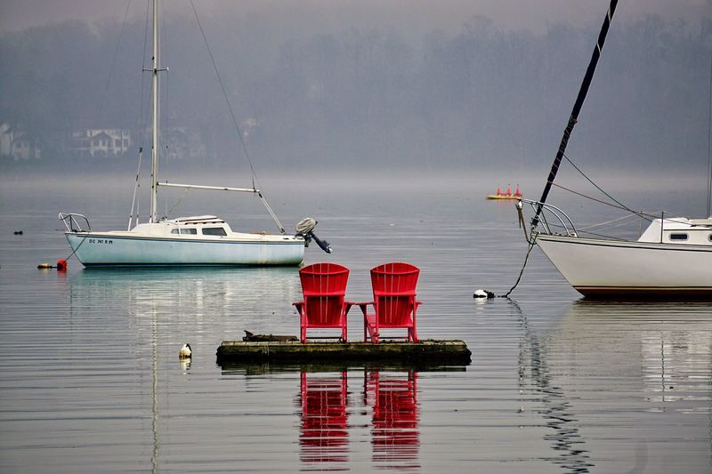 Frontal View Of Two Wooden Chairs On Water Platform