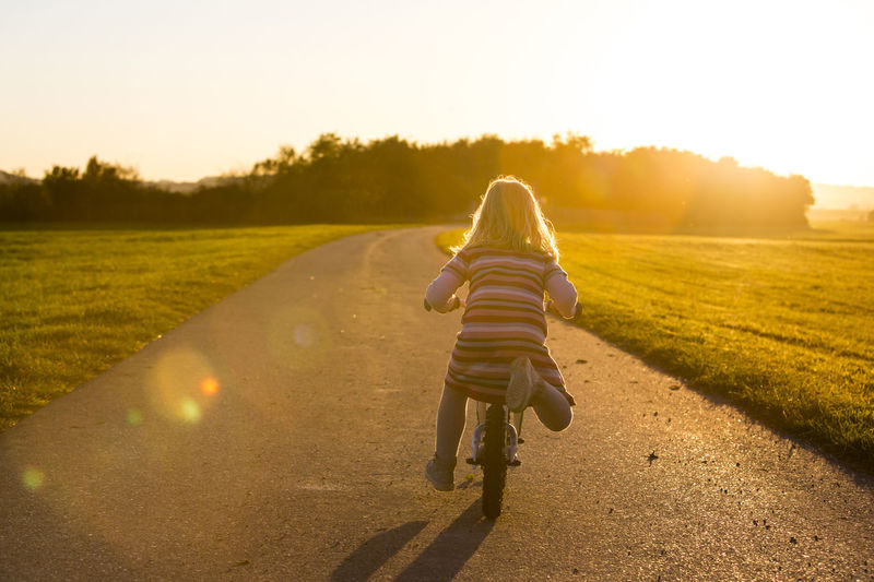 Rear view of girl riding bicycle on road amidst field during sunset