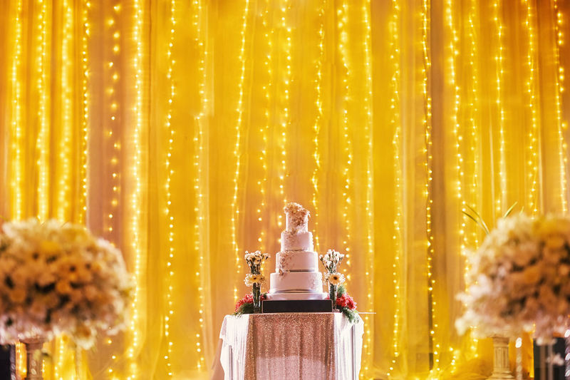 Layered cake on table against illuminated curtain
