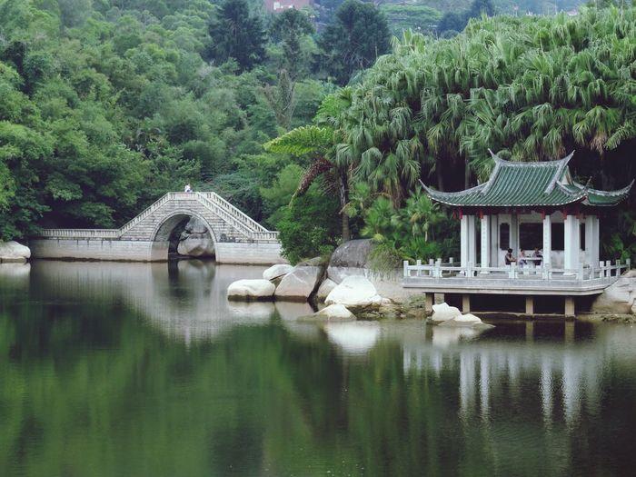 Gazebo reflection in lake against trees