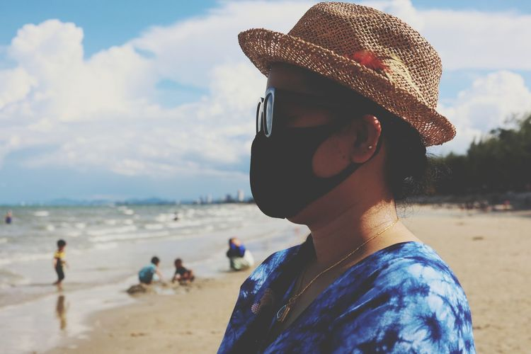 Close-up of woman wearing mask standing on beach