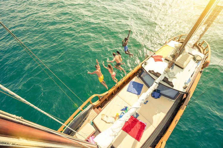 Aerial view of young people jumping from sailing boat on sea trip - Rich happy friends having fun in summer party day - Exclusive vacation concept - Warm vintage filter with enhanced sun flare halos Sailboat Sailing Boat Sail Sailing Boat Party Travel Exclusive  Sea Cruise Ship Trip Holiday Fun Young People Friends Group Happy Luxury Jump Ibiza Yacht Island Summer