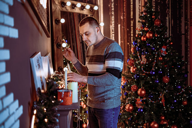 Man standing by christmas tree at home