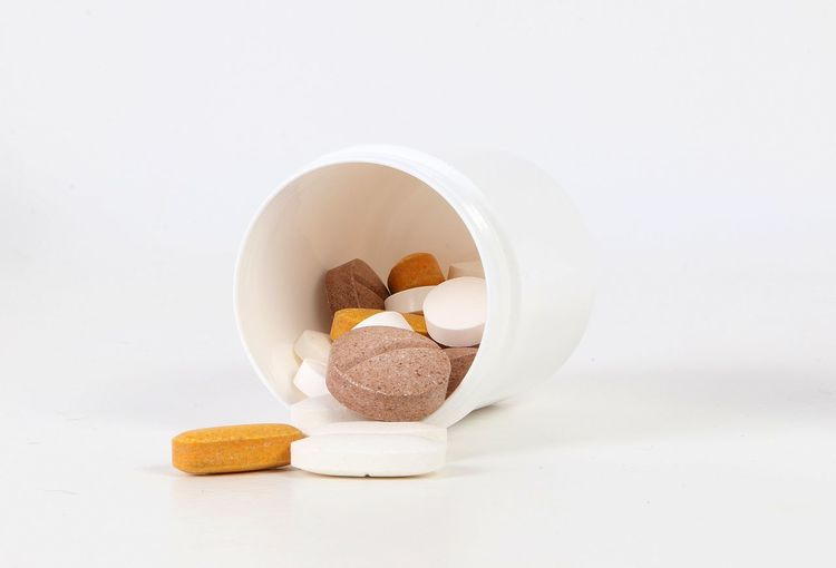 heap of different pills are lying with an open plastic tin in the white studio Pill Dose Container Studio Shot Studio Illness Cancer White Background Medicine Healthcare And Medicine Indoors  Food And Drink Wellbeing Close-up White Color Capsule Vitamin Healthy Eating Still Life Cut Out Dieting Tablets Pharmacy Pharmaceutical Medical