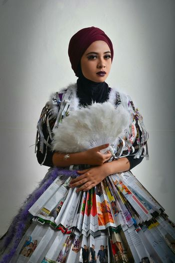 Portrait of young woman wearing newspaper costume against gray background