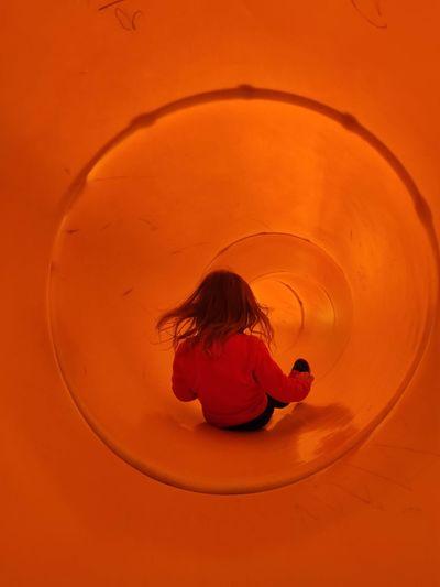 Rear view of little girl in a orange slider