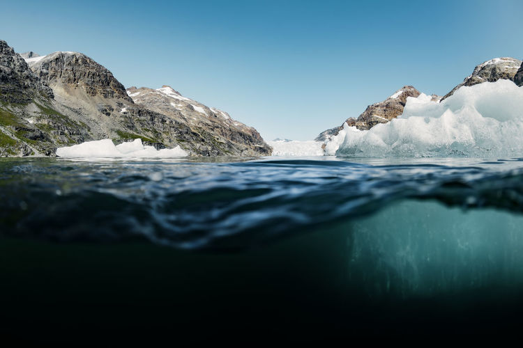 50/50 Global Warming Greenland Melting Melting Glacier Arctic Beauty In Nature Blue Climate Change Cold Temperature Environment Frozen Glacier Ice Iceberg Melting Ice Nature No People Scenics - Nature Sea Split Image Tranquil Scene Underwater Water Waterfront