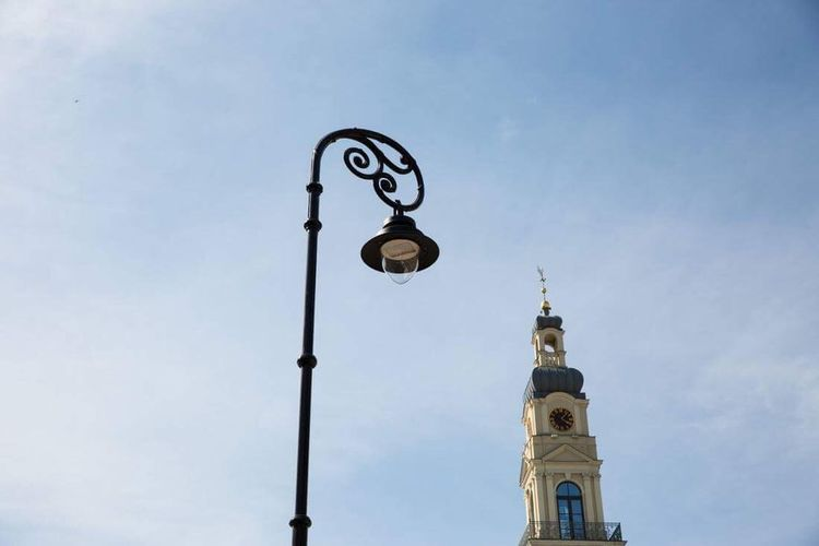 Low angle view of street light by building against sky